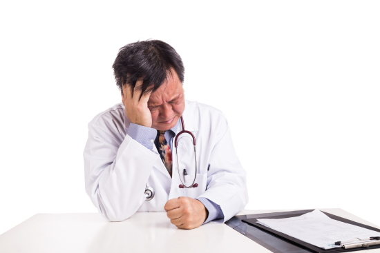 Depressed sad matured Asian doctor seated behind desk on white background